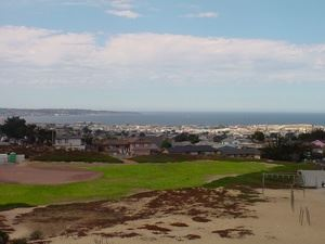 Baseball field grass and sand overlooking ocean and city