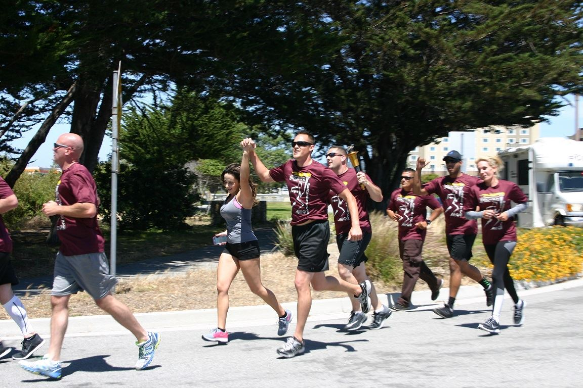 Group of Torch Run participants running on road near Laguna Grande park