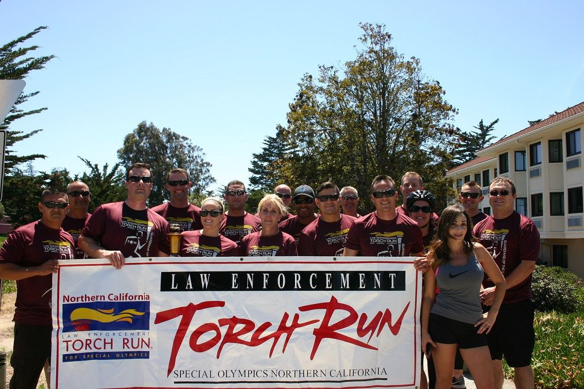 Group of Seaside and Monterey PD Torch Run participants standing behind event banner