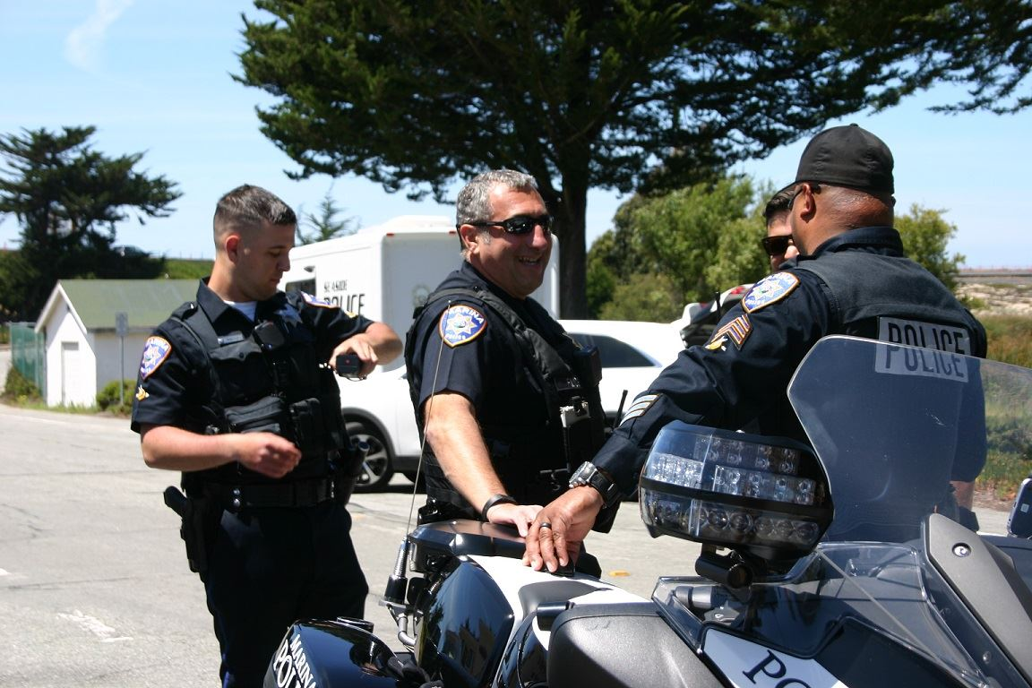 Four Officers standing behind motorcycle